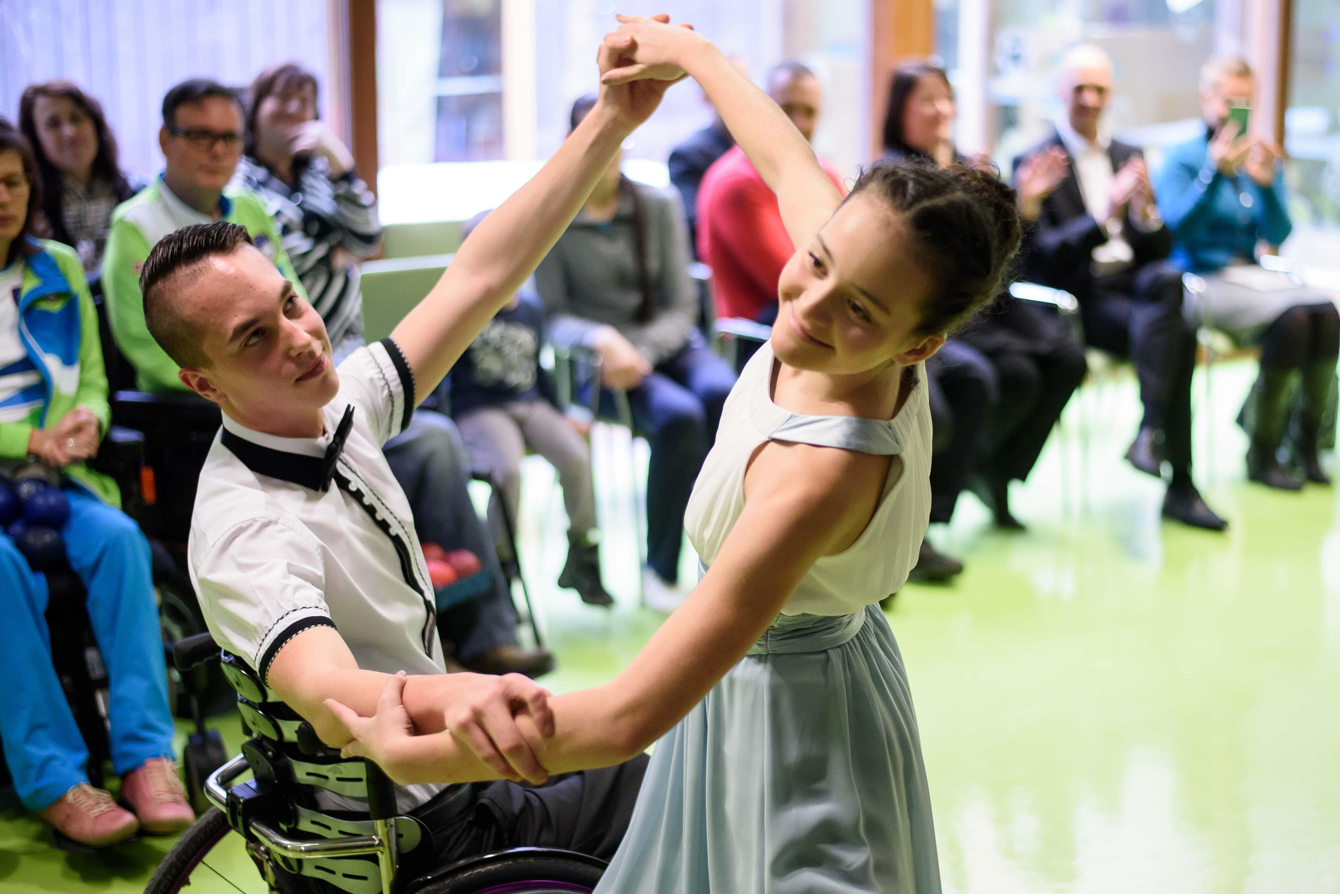 Deklica pleše s fantom na invalidskem vozičku