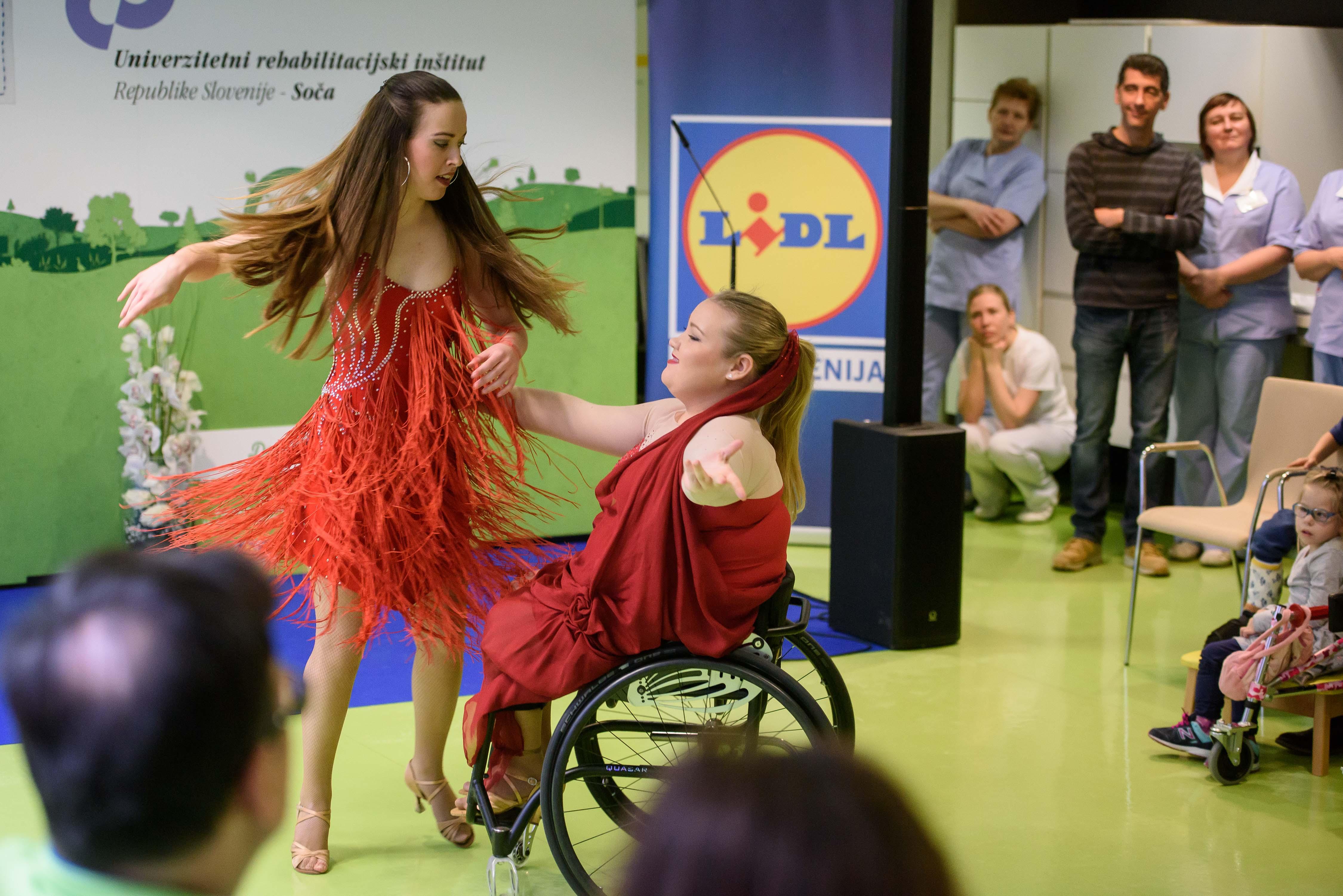 Dve dekleti plešeta, ena od njiju je na invalidskem vozičku